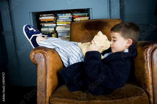 little boy lying in armchair with teddy bear