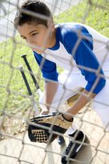 Boy in baseball gear sitting on a bench
