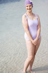 Senior woman in a swimsuit and swimming hat, at the beach