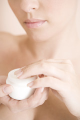 Young woman with pot of moisturising cream