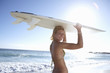 Young woman in bikini standing on beach in bright sunlight, carrying surfboard on head, portrait