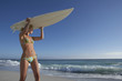 Young woman in bikini standing on beach, carrying surfboard on head, looking at horizon over sea