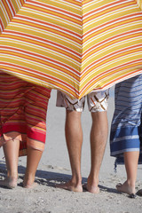 Three friends standing behind on sunshade on beach, side by side, low section, rear view