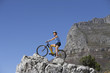 Female mountain biker sitting on bicycle at edge of rock, looking at view, side view, low angle view