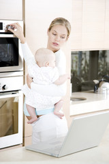 Young mother multi-tasking - holding baby, cooking dinner and looking at laptop