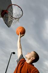 A teenage boy playing basketball