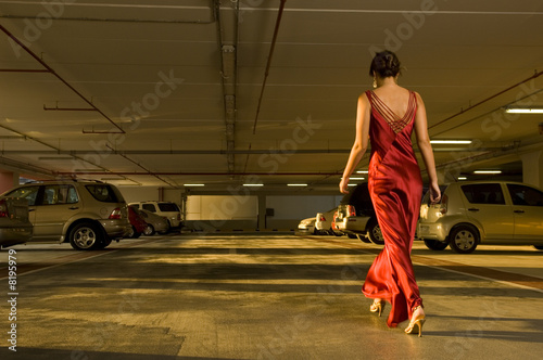 A woman in evening dress walking in a car park