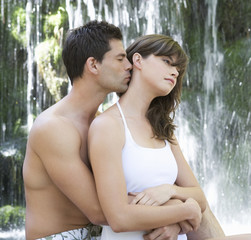 A couple kissing by a waterfall