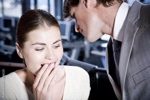Two business colleagues whispering to each other