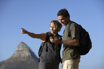 Couple hiking, man holding navigation system, woman pointing, smiling, mountain in background