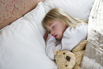 Young girl asleep in her bed with a teddy bear