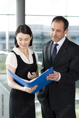 Male and female business colleagues looking at notes in a folder