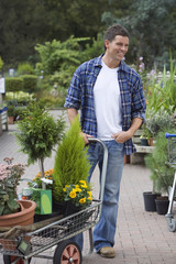 Man shopping in garden centre, pushing trolley full with pot plants, smiling