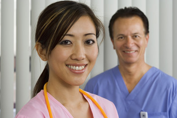 Doctor and nurse in surgical scrubs standing in hospital room, smiling, portrait