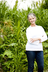 Portrait of a smiling senior woman in front of tropical foliage