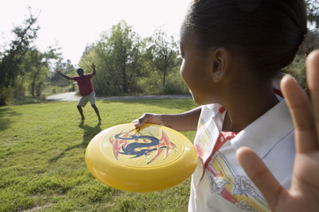 Girl (11-13) playing frisbee with father in park, smiling, close-up, rear view
