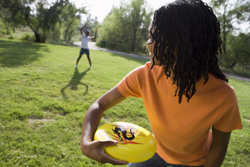 Woman playing frisbee with daughter (11-13) in park, smiling, focus on foreground (tilt)
