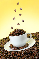 Coffee beans falling over a coffee cup