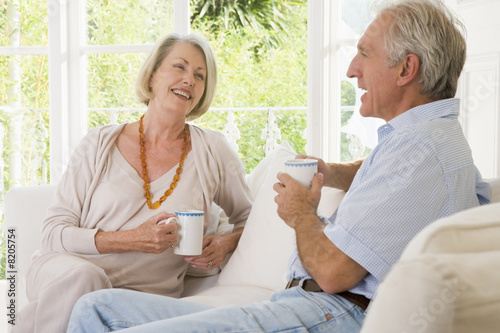 Couple in living room with coffee smiling Poster