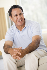Man sitting in living room smiling