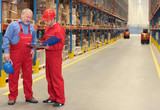 standing workers in warehouse reading invoice poster