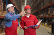 older worker showing something to another in warehouse
