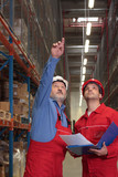 two checking workers in uniforms and hardhats in warehouse poster