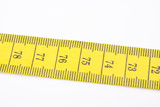 yellow measuring tape used by tailors on white poster