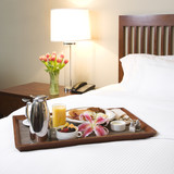 Fototapety Breakfast tray on white bed.