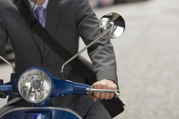Man riding on scooter in street, mid-section, front view, close-up