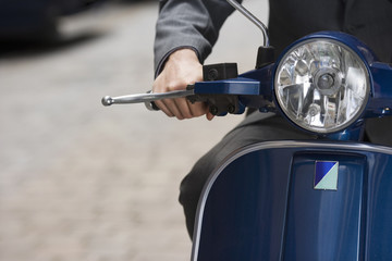 Man riding on scooter in street, mid-section, front view, close-up, focus on headlight