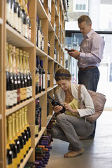 Customers shopping in off-licence, looking at bottles of wine on shelf, woman crouching, side view