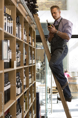 Shop owner looking at bottle of wine in off-licence, standing on step ladder beside shelf, side view
