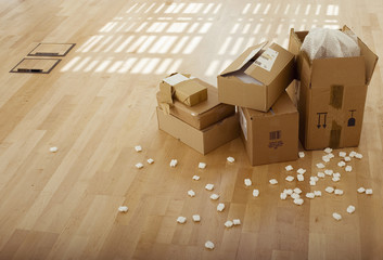Stack of cardboard boxes beside packing foam on wooden floor in empty office