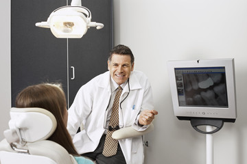 Male dentist showing x-ray of teeth on visual screen to patient, woman sitting in dentist's chair