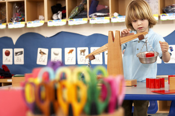 Multi-coloured scissors in classroom, focus on boy (4-6) playing with weight scale in background