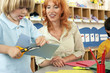 Two boys (4-6) cutting piece of card at desk in classroom, teacher assisting, smiling