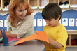 Boy (4-6) cutting piece of orange card at desk in classroom, teacher assisting, smiling