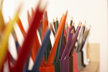 Row of multi-coloured colouring pencils in pots, close-up (still life, differential focus)
