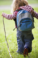 Girl (4-6) hiking on grass, carrying rucksack, holding stick, rear view
