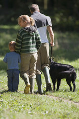 Two generation family walking dog in countryside, wearing wellington boots, rear view