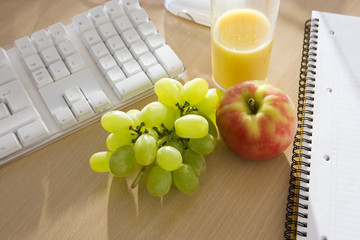 Bunch of grapes, apple and orange juice on office desk, close-up, elevated view (still life)