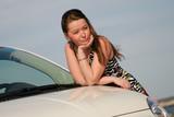 pretty woman leans her elbows on a car bonnet poster