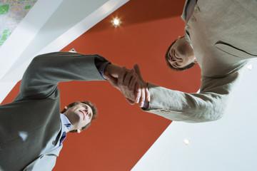 Two businessmen shaking hands, upward view (tilt)