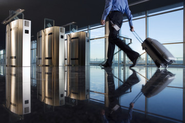 Man with luggage walking towards security barrier, low section, surface level, reflection on floor