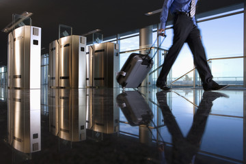 Man with luggage walking away from security barrier, low section, surface level, reflection on floor