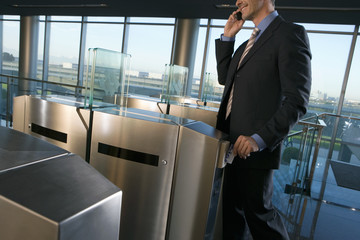 Businessman placing card in security barrier, using mobile phone, smiling, side view (tilt)