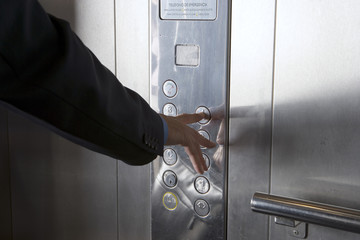 Businessman pushing elevator button, close-up, mid-section