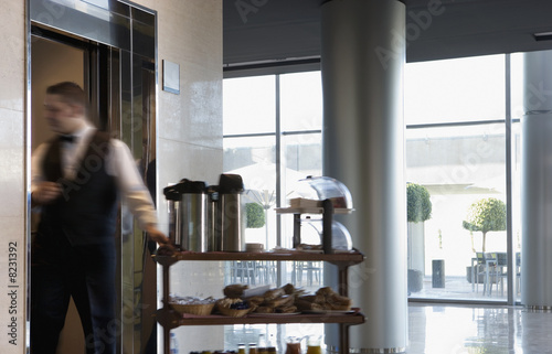 Waiter entering elevator in lobby, pulling food and drinks trolley, side view