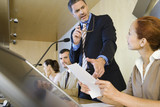 Businessman standing in conference room, pointing to document in businesswoman's hands, side view